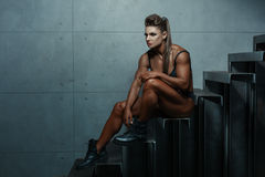 Woman with big muscles while sitting. royalty free stock photos