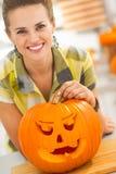 Woman with a big orange pumpkin Jack-O-Lantern in kitchen Stock Images