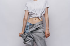 Woman in big pants on a gray background, fitness, slender waist, slenderness.  Royalty Free Stock Photo