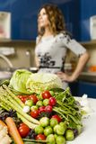 Woman with a big pile of vegetables Royalty Free Stock Photography