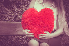Woman with big red heart. Love and feelings. Part body woman sitting on bench with big red heart in hands. Girl in park Royalty Free Stock Photography