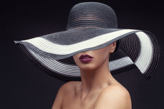 Woman in big summer hat. Beautiful young woman wearing summer hat with large brim over dark background royalty free stock photography