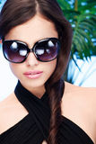 Woman with big sun glasses. Beautiful woman with big sun glasses and long hair in front of a palm tree royalty free stock photography