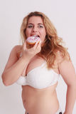 Woman with big tits eats a colorful muffin. Stock Photo