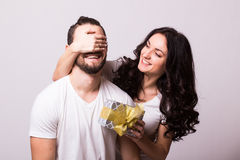 Woman with big toothy smile holding boyfriends eyes giving him a present for Valentine's day. Attractive happy women with big toothy smile holding boyfriends Royalty Free Stock Images