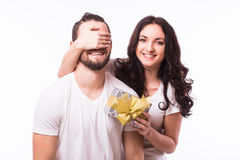 Woman with big toothy smile holding boyfriends eyes giving him a present for Valentine's day. Attractive happy women with big toothy smile holding boyfriends royalty free stock photography
