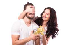 Woman with big toothy smile holding boyfriends eyes giving him a present for Valentine's day. Attractive happy women with big toothy smile holding boyfriends royalty free stock image