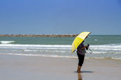 Woman with big umbrella waiting for someone on the the beach Stock Images