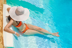 Woman in big whire hat relaxing on the swimming pool Royalty Free Stock Image