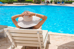 Woman in a big white hat relaxing on a lounger by the pool Royalty Free Stock Photo