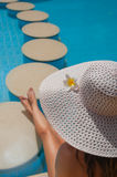 Woman in a big white hat sits on the edge of the pool with stones Royalty Free Stock Photos