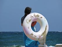 Woman with Big White Inflatable Swimming Ring Standing on Beach During Summer Vacation royalty free stock photo