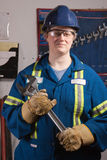 Woman with big wrench. Woman mechanic working in a workshop holding a large wrench wearing protective gloves royalty free stock images