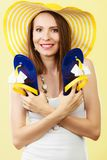 Woman in big yellow summer hat holds flip flops. Holidays summer fashion concept. Woman in big yellow hat holding flip flops in hand bright background stock images