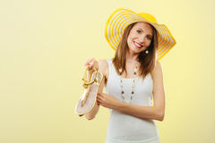 Woman in big yellow summer hat holds sandals Royalty Free Stock Image
