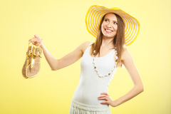 Woman in big yellow summer hat holds sandals Royalty Free Stock Photography