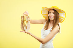 Woman in big yellow summer hat holds sandals Stock Image