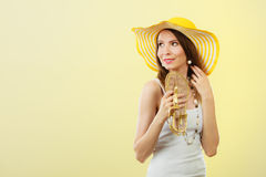 Woman in big yellow summer hat holds sandals Stock Photography