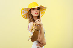Woman in big yellow summer hat holds sandals Stock Photo