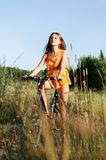 Woman with bike. Young beautiful woman with bike on the meadow Royalty Free Stock Image