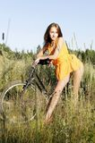 Woman with bike. Young beautiful woman with bike on the meadow Royalty Free Stock Photo