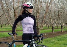 Woman with Bike. Woman posing with her bike in an orchard Stock Photography