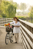Woman with bike. Middle-aged Woman with bike by the river Royalty Free Stock Photo