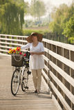 Woman with bike. Walking by the river Royalty Free Stock Image