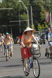 Woman on bike with asian conical hat Stock Photography