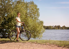 Woman with a Bike on Beautiful Nature Background Royalty Free Stock Image