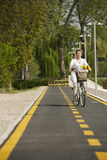 Woman with bike on the bikeway. Middle-aged woman with bike on the bikeway Stock Images
