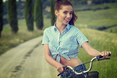 Woman with bike in a country road. Royalty Free Stock Image