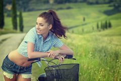 Woman with bike in a country road. Stock Photos