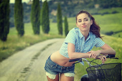 Woman with bike in a country road. Royalty Free Stock Images