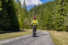 Woman on bike in forest. Happy girl on bike in forest at Ludrovska valley in Slovakia royalty free stock photography