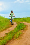Woman with bike on green field Royalty Free Stock Photo