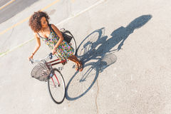 Woman with bike with her shadow on the road. Stock Photography