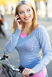 Woman on bike with mobile phone Royalty Free Stock Photos