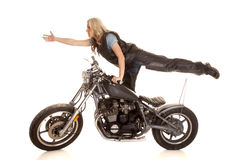 Woman on bike one leg up hand out stock photos