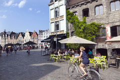 Woman on bike and outdoor café near groentenmarkt in centre of Royalty Free Stock Image