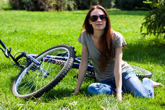 Woman with bike outdoors. Girl sitting next to Bicycle on nature Stock Photography