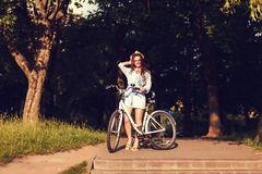Woman with bike outdoors. Attractive young tourist woman visiting a destination city with bike outdoors Stock Photos