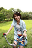 Woman with a bike outdoors smiling. In the park Royalty Free Stock Photo