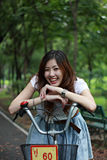 Woman with a bike outdoors smiling. In the park Royalty Free Stock Photography