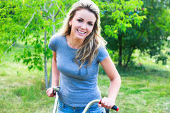 Woman on bike. Outdoors smiling Royalty Free Stock Images