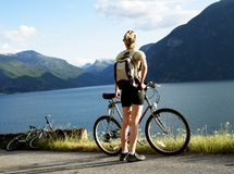 Woman with bike over the fjord. Sporty woman with her bike looking at the mountain stock images