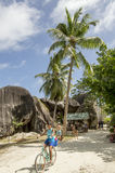 Woman on bike in path in La Digue, Seychelles. La Digue, Seychelles - August 12, 2015: Woman on bike riding through path in La Réunion, the entrance to Anse Royalty Free Stock Image