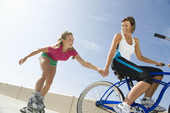 Woman On Bike Pulling Friend On In-Line Skates Royalty Free Stock Photography