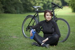 Woman with bike resting on ground Royalty Free Stock Photography
