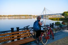 Woman on a bike ride in the park along the river. Woman on a bike ride in the park along the Dnepr River, Kiev, Ukraine royalty free stock photo